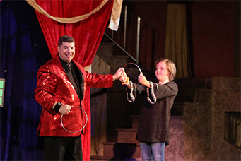 joseph young with volunteer for a magic show