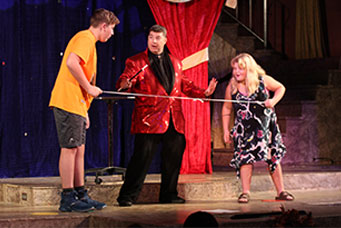 joseph young with two volunteers performing magic